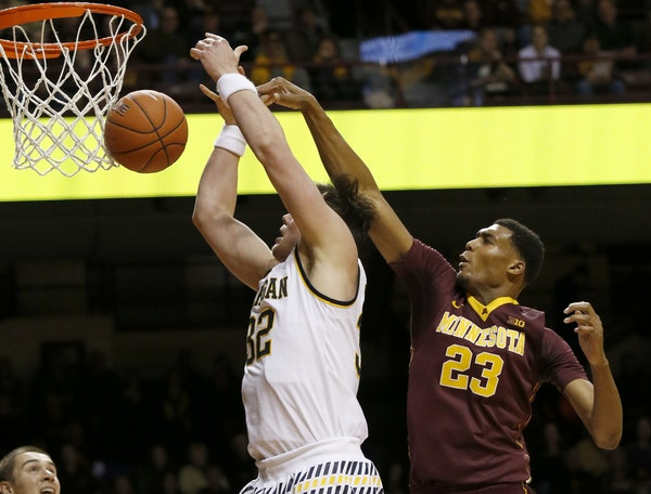 Michigan forward Ricky Doyle (32) loses control of the ball as he is fouled by Minnesota forward Charles Buggs (23) during the first half of an NCAA c