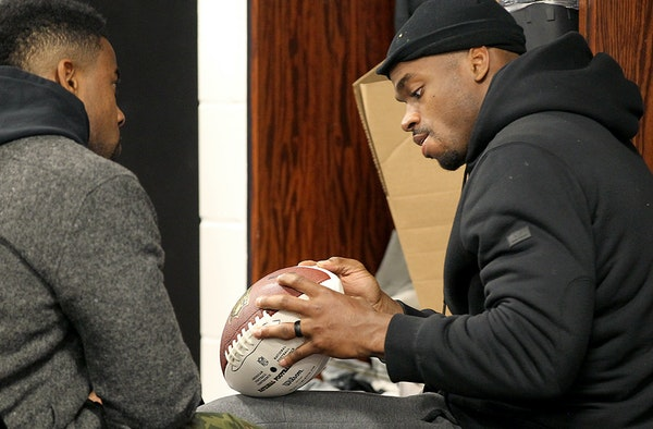 Adrian Peterson, signing a football for teammate Antone Exum Jr. on Monday at Winter Park, vowed to improve his ball security in the offseason.