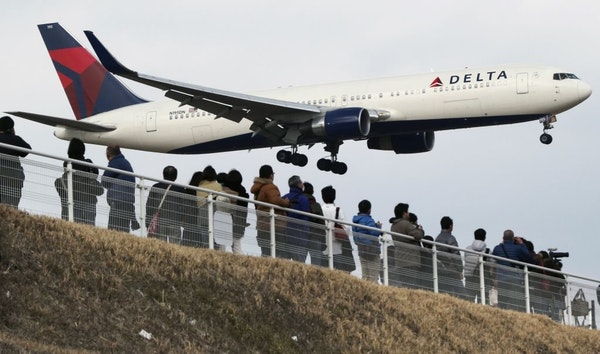 In this March 14, 2015, file photo, people watch a landing Delta Air Lines jet approach the Narita International Airport from a popular viewing spot a
