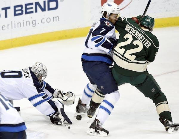 Winnipeg Jets goalie Connor Hellebuyck (30) covers up the puck as defenseman Ben Chiarot (7) pushes Minnesota Wild right wing Nino Niederreiter (22),