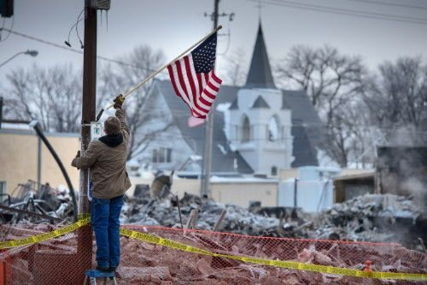 Madelia street supervisor Mark Blekestad placed American flags along Main Street, where a fire this week destroyed six buildings on a downtown block.