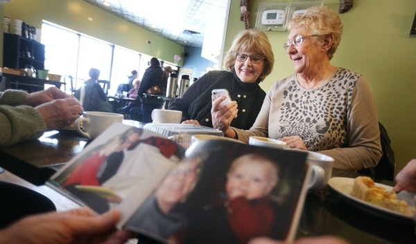 Joan Brown of Inver Grove Heights, left, and Joanne Yamka of South St. Paul looked at photos and talked some politics at the Black Sheep Coffee Cafe o