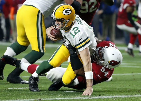 Packers quarterback Aaron Rodgers found himself on the turf repeatedly Sunday, here getting dragged down by veteran Cardinals pass-rusher Dwight Freen