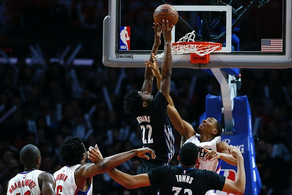 The Los Angeles Clippers' Wesley Johnson reaches through the net to defend the shot of the Minneota Timberwolves' Andrew Wiggins during second-half ac