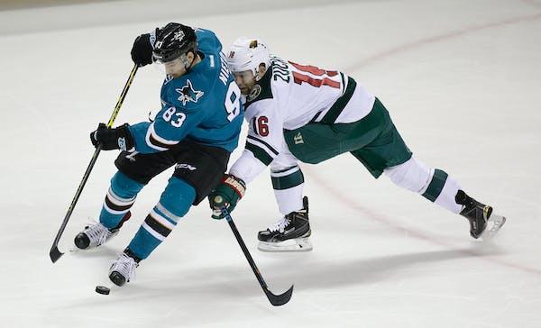 San Jose Sharks left wing Matt Nieto, left, and Minnesota Wild left wing Jason Zucker, right, battle for the puck in the first period of an NHL hockey