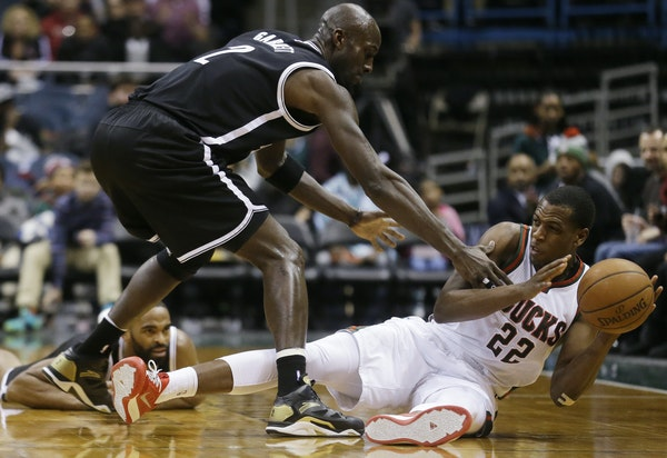 Milwaukee Bucks' Khris Middleton (22) tries to pass the ball with Brooklyn Nets' Kevin Garnett (2) defending during the second half of an NBA basketba