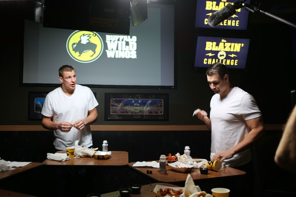 New England Patriots tight end Rob Gronkowski (left) takes Buffalo Wild Wings' Blazin Challenge with his brother Dan (right).
