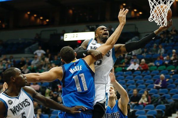 Minnesota Timberwolves forward Shabazz Muhammad (15) pushes the ball up to the basket against Dallas Mavericks center JaVale McGee (11) in the first h