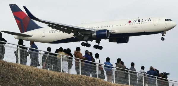 FILE - In this March 14, 2015 file photo, people watch a landing Delta Air Lines jet approach the Narita International Airport from a popular viewing