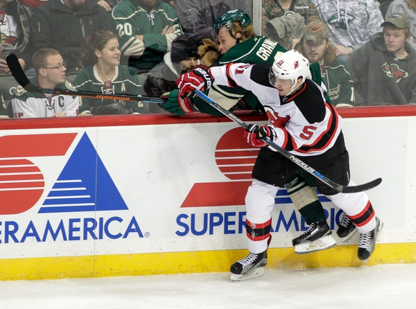 Minnesota Wild center Mikael Granlund, of Finland, is driven hard into the boards by New Jersey Devils defenseman Adam Larsson (5), of Sweden, during