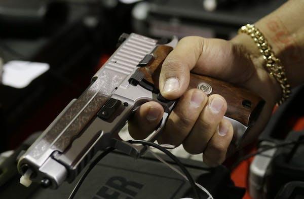 A customer looks at a SIG Sauer hand gun at a gun show held by Florida Gun Shows, Saturday, Jan. 9, 2016, in Miami. President Barack Obama announced p