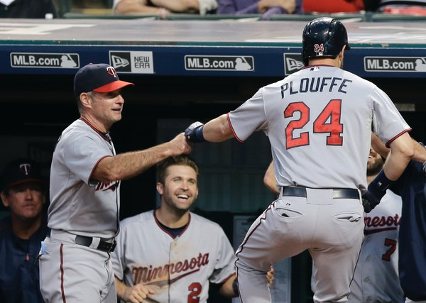 Minnesota Twins manager Paul Molitor, left congratulates Trevor Plouffe after Plouffe hit a two-run home run in the first inning of a baseball game ag
