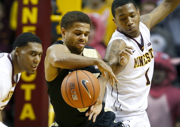 Purdue guard P.J. Thompson, center, and Gophers guard Dupree McBrayer (1) clawed after possession of the ball during the Boilermakers' 68-64 victory