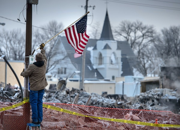 Madelia street supervisor Mark Elekestad hung American flags along Main Street in front of the block devastated by fire.