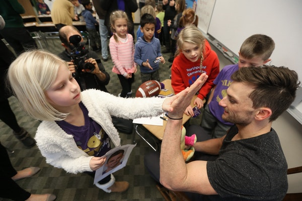 Kyleigh Duerr left gave a high five to Minnesota Vikings kicker Blair Walsh after giving him a stuffed animal. Walsh thanked first graders at Northpoi