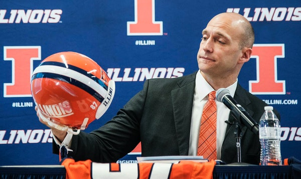 Josh Whitman, holds up his old football helmet as he is announced as the new the new Illinois athletic director during a news conference at Bielfeldt