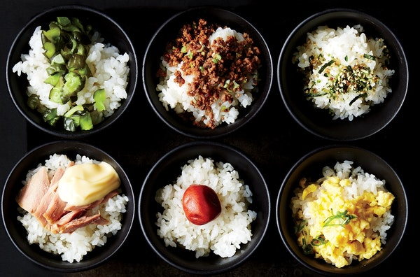 Toppings for rice include, from top left, pickled cucumber, Soboro beef, Furikake seasoning, and, from bottom left, tuna and mayo, pickled plum, and s
