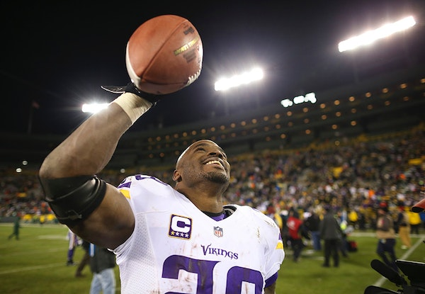 Vikings running back Adrian Peterson (28) held one of the game balls aloft as he walked off the field after the Vikings regular-season-finale win Sund