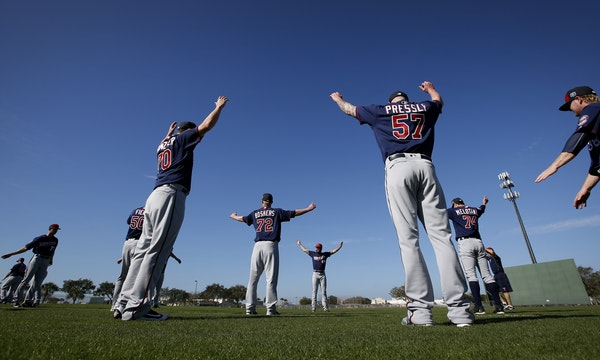 Minnesota Twins pitcher Ryan Pressly (57) and teammates stretched out at the beginning of practice. Monday was the first organized practice of spring