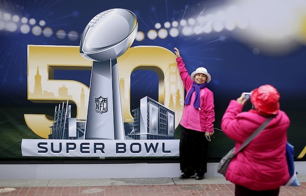Angie Bagares poses for a photo Wednesday in front of a Super Bowl 50 sign at Super Bowl City in San Francisco.