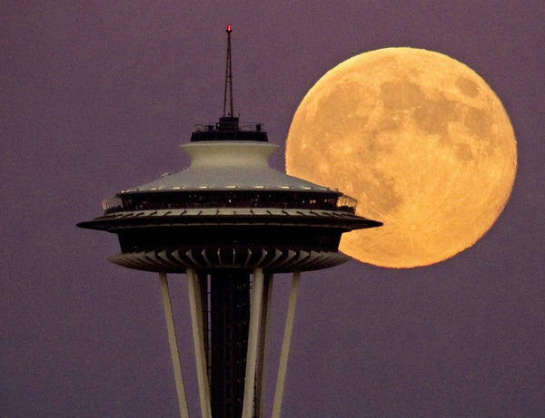 A full moon rises besides the Space Needle, Monday July 22, 2013, in Seattle. This view is from the Ursula Judkins Viewpoint, part of Smith Cove Park,