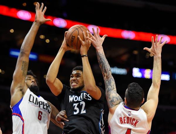 Minnesota Timberwolves center Karl-Anthony Towns, center, shoots as Los Angeles Clippers center DeAndre Jordan, left, and guard J.J. Redick defends du