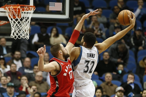 Minnesota Timberwolves center Karl-Anthony Towns (32) stretches out to shoot the ball against Toronto Raptors center Jonas Valanciunas (17) in the sec
