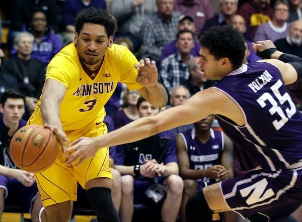 Minnesota forward Jordan Murphy, left, controls the ball against Northwestern forward Aaron Falzon during the first half of an NCAA college basketball