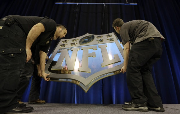 Workers hung an NFL shield before a news conference Thursday in San Francisco. Minnesota will be the Super Bowl site in 2018.