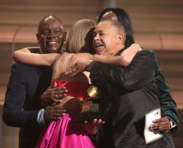 Philip Bailey, from left, Verdine White, obscured, and Ralph Johnson of Earth Wind & Fire present Taylor Swift the award for album of the year for '19