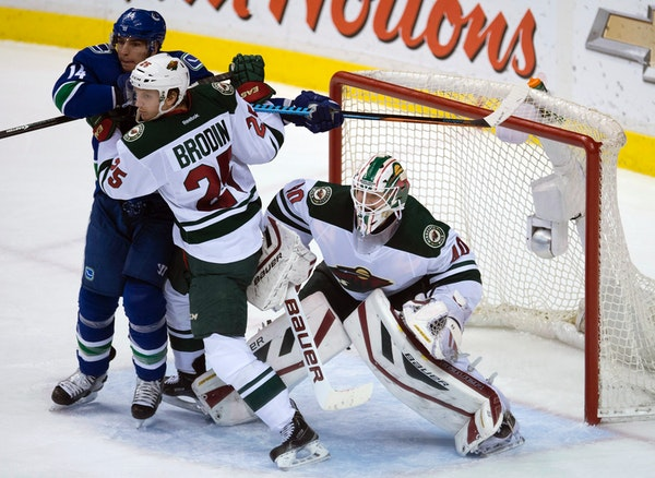 Wild defenseman Jonas Brodin tried to clear Canucks left winger Alex Burrows from in front of Wild goalie Devan Dubnyk during the second period of the