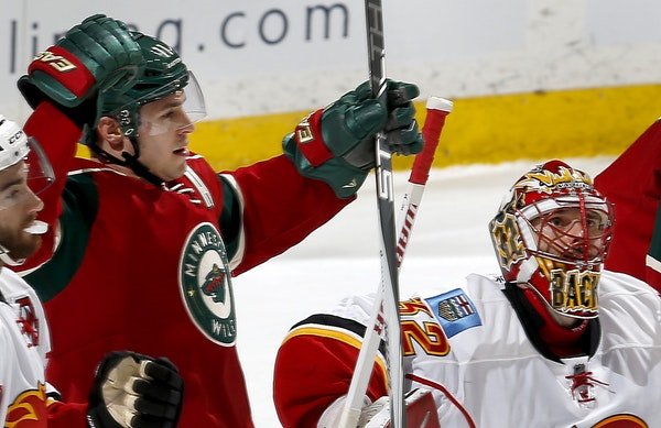 After shooting the puck past Calgary Flames goalie Niklas Backstrom, Zach Parise (11) celebrated after scoring his third goal in the first period.
