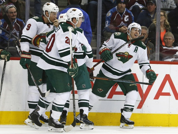 Minnesota Wild left wing Zach Parise, right, celebrates after scoring a goal against the Colorado Avalanche in the second period of an NHL hockey game