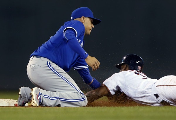 Toronto Blue Jays second baseman Ryan Goins, left, tags out Minnesota Twins' Danny Santana on an attempted steal of second base during the 11th inning