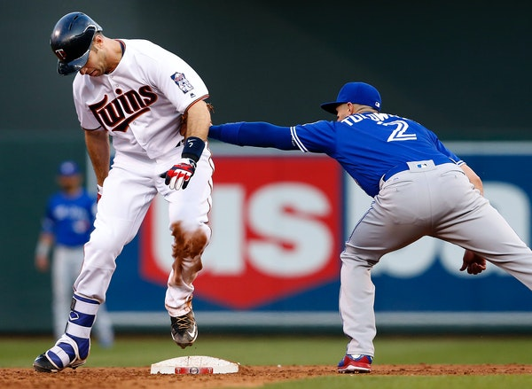Joe Mauer (7) was tagged out by Troy Tulowitzki (2) after stepping off the bag while trying to advance to second base after hitting an RBI single in t