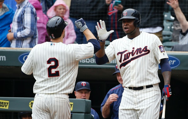 Miguel Sano, right, congratulates teammate Brian Dozier on Dozier's solo home run off Kansas City Royals starting pitcher Dillon Gee.