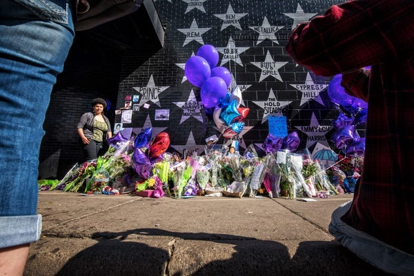 People filed past the makeshift memorial next to Prince's star on First Avenue's wall of stars. They took photos and posed for their own, left letters