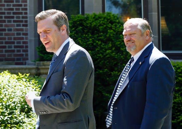 Republican House Speaker Kurt Daudt, left, and Senate Majority Leader Tom Bakk smile at reporters as they arrive at the governor's residence earlier t