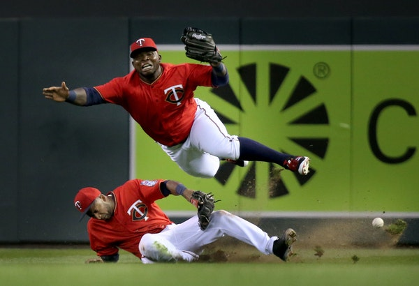 Minnesota Twins right fielder Miguel Sano, top, and second baseman Eduardo Nunez collide in right field while chasing a fly ball hit by the Los Angele