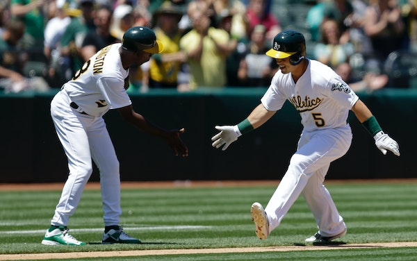 Oakland Athletics' Jake Smolinski, right, is congratulated by third base coach Ron Washington after hitting a home run off Minnesota Twins pitcher Pat