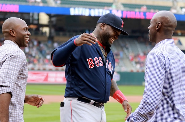 During a pre-game ceremony honoring Boston Red Sox and former Minnesota Twin David Ortiz, Ortiz is greeted by former Twin teammates LaTroy Hawkins, ri