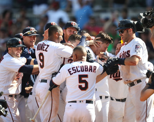 The Twins' Max Kepler mobbed by teammates after his three-run homer won the game in the 10th inning Sunday afternoon.