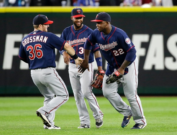 Minnesota Twins outfielders Robbie Grossman (36), Danny Santana and Miguel Sano (22) share congratulations after they defeated the Seattle Mariners in