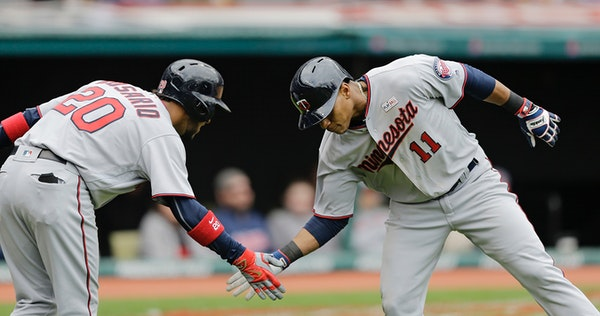 Minnesota Twins' Jorge Polanco, right, is congratulated by Eddie Rosario after Polanco hit a solo home run off Cleveland Indians starting pitcher Trev
