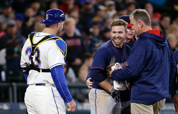 Minnesota Twins' Brian Dozier smiles as he looks across at Seattle Mariners catcher Chris Iannetta (33) as Dozier is checked after being hit by a pitc