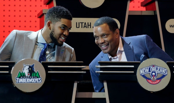 Minnesota Timberwolves center Karl-Anthony Towns, left, talks with New Orleans Pelicans head coach Alvin Gentry before the start of the NBA basketball
