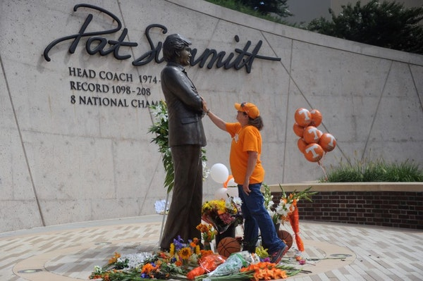Teresa Olive, of Knoxville, Tenn., touches a statue of Pat Summitt as she pays her respects at the University of Tennessee, on Tuesday, June 28, 2016,
