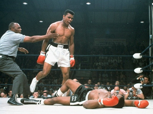 FILE - In this May 25, 1965, file photo, heavyweight champion Muhammad Ali is held back by referee Joe Walcott, left, after Ali knocked out challenger