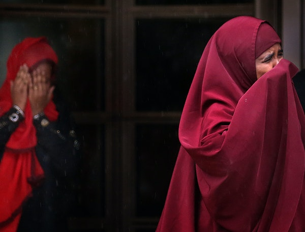Farhiyo Mohamed, right, the mother of defendant Abdirahman Daud, and a second woman emerge in tears from the federal courthouse in Minneapolis on Frid