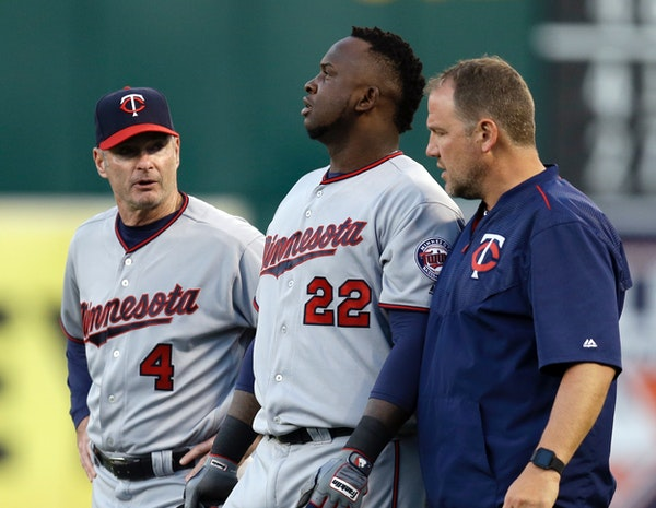 Minnesota Twins manager Paul Molitor, left, and a trainer walk Miguel Sano (22) off the field after an injury sustained in the third inning of a baseb